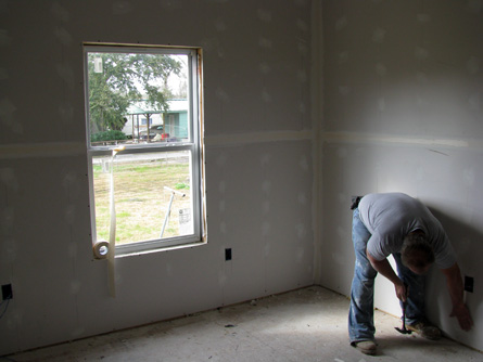 A Hope Force volunteer installs sheetrock in the bedroom.